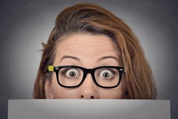 Scared surprised woman peeking over edge of blank billboard