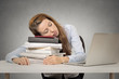 tired woman student sleeping on books at her desk