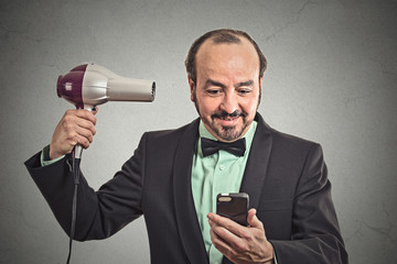 man reading news on smartphone blowing hair with hairdryer