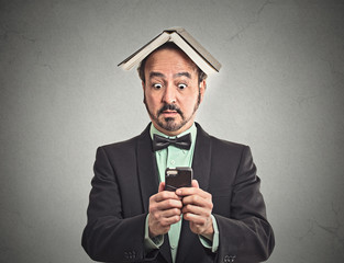 surprised man reading news on smart phone on grey background