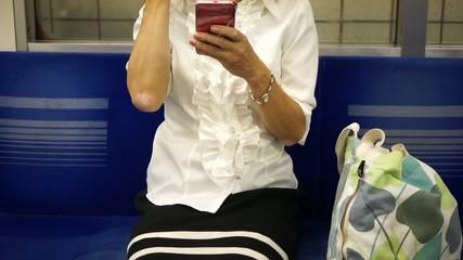 電車の車内でスマートフォンを操作する女性