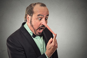 Liar man with long nose isolated on grey wall background