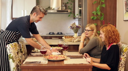 Man preparing pizza for women at home