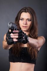 Beautiful sexy police girl with handgun and  isolated on grey ba