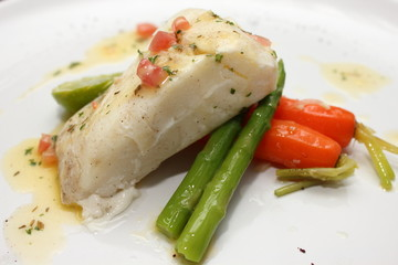 grilled Pangasius fish steak, isolated on a white plate