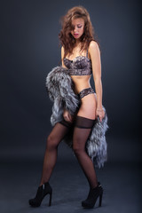 Attractive woman in fur coat and bra
