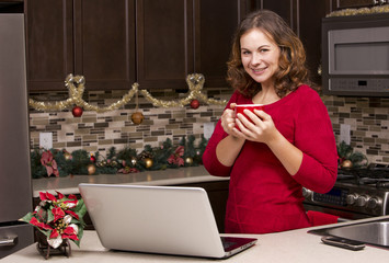 woman with laptop in Christmas kitchen