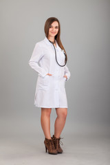 Young and beautiful nurse on a grey
