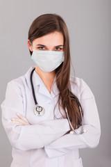 Doctor / nurse smiling behind surgeon mask. Closeup portrait of