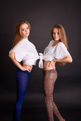 Two beautiful girls twins, on black