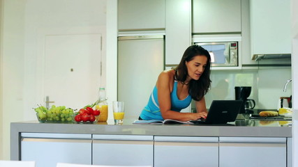 Woman working on laptop in the kitchen, steadycam shot