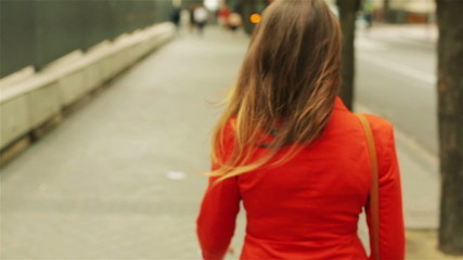 Woman in red jacket walking on the street, steadycam shot