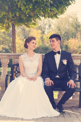 Beautiful bride and groom sitting on bench