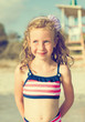 Portrait of happy little girl on the beach. Vintage effect.