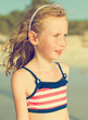 Portrait of little girl on the beach. Vintage effect.