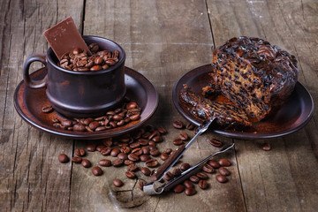 Roasted coffee beans and fruit cake over rustic wooden backgroun
