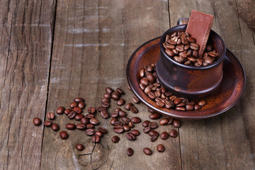 Roasted coffee beans over rustic wooden background