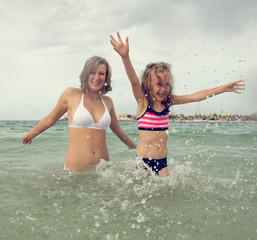 Woman and her daughter having fun in the sea.