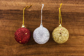 christmas ball red,silver,gold on wood background.