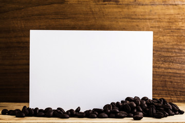 Paper with coffee bean on wood background.