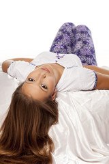 calm young girl with long hair lying on the bed