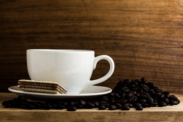 warm cup of coffee with bean on wood background