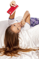 young woman with long hair lying on the bed and make a selfie