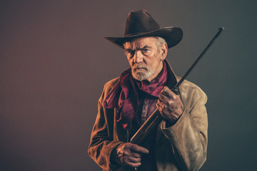 Old rough western cowboy with gray beard and brown hat holding r