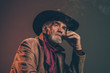 Old rough western cowboy with gray beard and brown hat smoking a - 71983720
