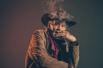 Old rough western cowboy with gray beard and brown hat smoking a