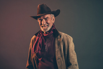 Smiling old rough western cowboy with gray beard and brown hat.