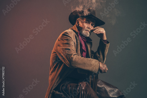 Old rough western cowboy with gray beard and brown hat smoking a - 71983702