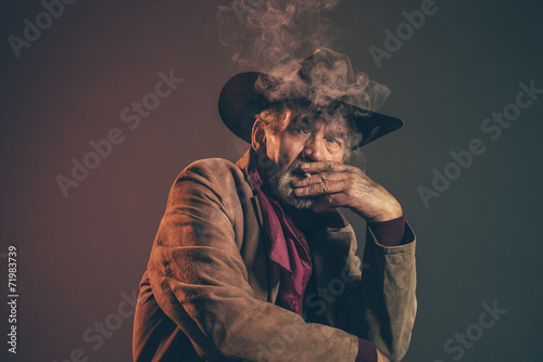 Old rough western cowboy with gray beard and brown hat smoking a - 71983739