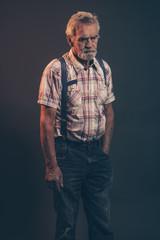 Characteristic senior man with gray hair and beard wearing check