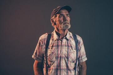 Characteristic senior man with gray hair and beard wearing blue