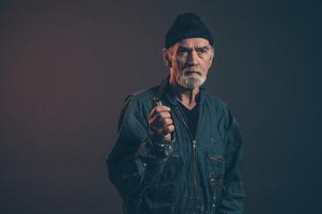 Senior carpenter with gray hair and beard holding sliding t beve
