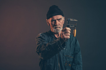 Senior carpenter with gray hair and beard holding clamp wearing
