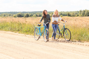 Two friends at their bike walking outdoors