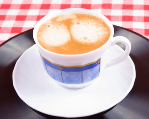 Cup of coffee on a vinyl record and red-white vichy tablecloth