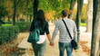 Couple walking in park and holding hands at autumn, steadycam