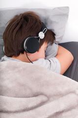 close-up portrait of a beautiful sleeping teenager in earphone