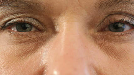 Closeup on eyes, mature woman opening eyes, looking left and rig