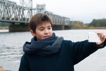 Boy in front of the railway bridge makes selfie