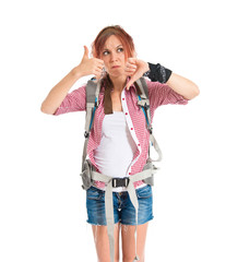 backpacker making a good-bad sign over white background