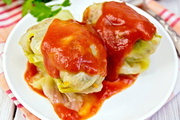 Cabbage stuffed and tomato sauce in plate on board