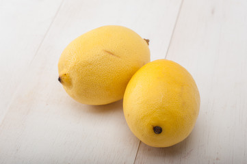 Close up of two lemons on white table