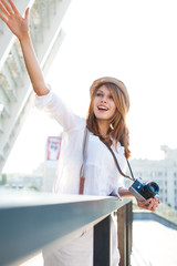 Travel tourist woman with camera waving to someone
