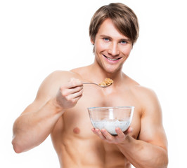 Young  muscular man eating flakes.