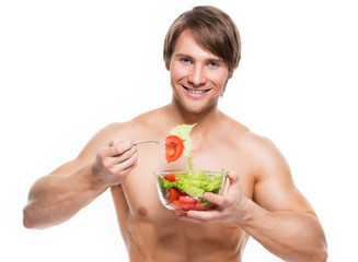 Happy muscular man eating a salad.