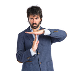 Serious man making time out gesture over white background